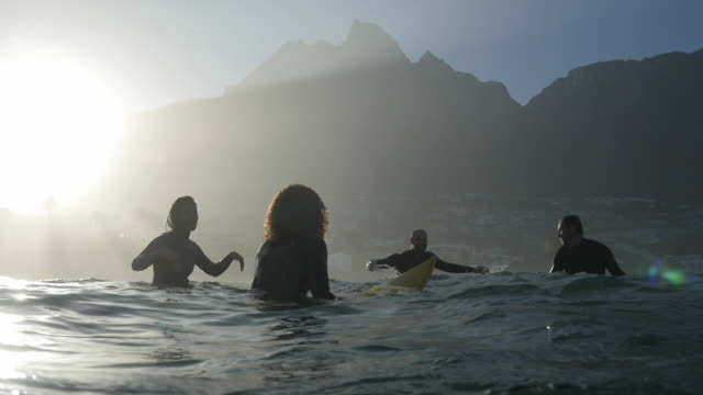 ws_four surfers in the ocean, waiting for waves - males stock videos & royalty-free footage