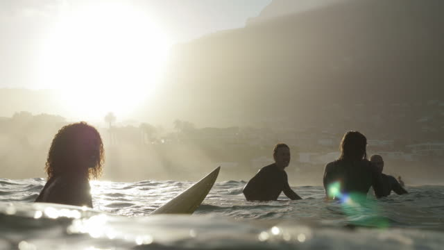 vídeos de stock, filmes e b-roll de ws_four surfers in the ocean, waiting for waves - surfe