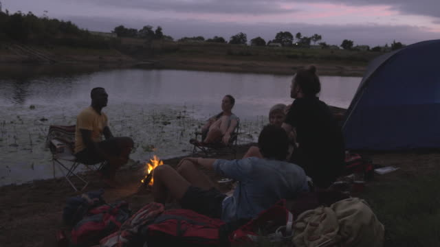 ws_friends hanging out, chatting & having a good time around bonfire at campsite - camping stock-videos und b-roll-filmmaterial