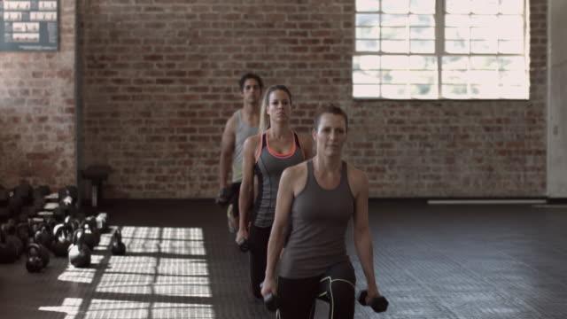 ws_gruppe von turnern, die lungen mit handgewichten in städtischen fitness-studio - sich verschönern stock-videos und b-roll-filmmaterial