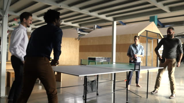 vídeos de stock, filmes e b-roll de ws_steady-cam_creative co-workers playing tabletennis, in open office - tênis de mesa