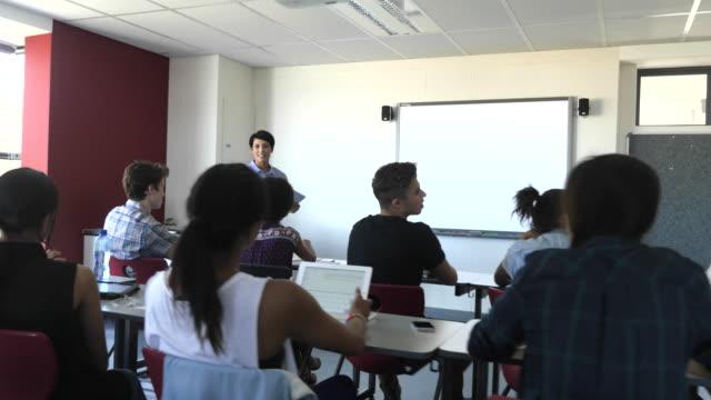 ws_steadycam_teacher explaining to class of students - braccia alzate video stock e b–roll