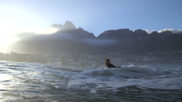 stockvideo's en b-roll-footage met ws_surfer paddling in the ocean - shaky