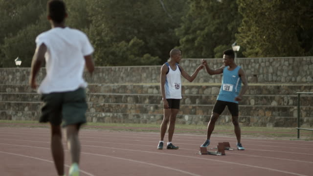 ws_track athletes chatting and relaxing, at stadium after practice - practising stock videos & royalty-free footage