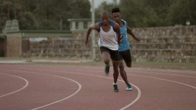 ws_track athletes passing baton in relay race - relay stock videos and b-roll footage