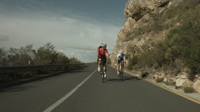 ws_two female pro cyclists riding down mountain road - pampering self stock videos and b-roll footage