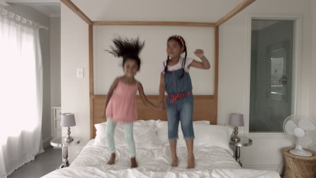 WS_Two girls jumping and smiling in bed