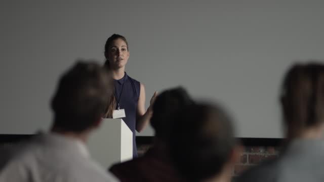 vidéos et rushes de ws_woman doing a speech at convention - petit groupe de personnes