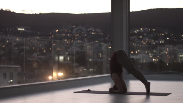 WS_Woman doing yoga poses at dusk, in rooftop studio