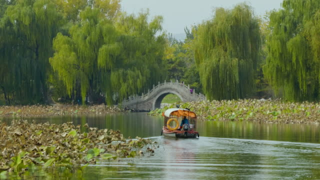 wsêboat on lake and arch bridge inêold summer palace, beijing, china - summer palace beijing stock videos & royalty-free footage