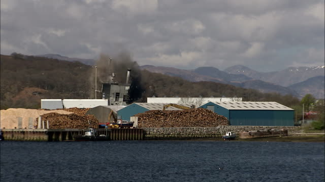 wsmill building on lake with mountains is demolished in  controlled implosion using explosives / for william, scotland, uk - imploding stock videos and b-roll footage