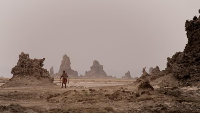wss elderly afar man walking near rocks - horn of africa stock videos & royalty-free footage