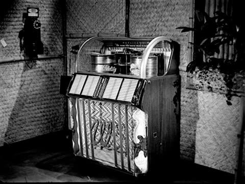 wurlitzer model 1550 jukebox backed against wall aside rotary dial pay telephone wurlitzer model jukebox on january 01 1954 - jukebox stock videos & royalty-free footage