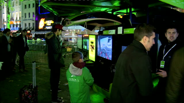 Xbox One Launch **Music heard SOT** Giant screen showing Xbox settings / XBox One balloo / paper lantern / people playing games / XBox One car /