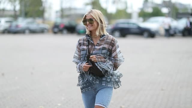 vídeos de stock, filmes e b-roll de xenia adonts wearing skinny denim shorts belt bag checked button shirt is seen outside holzweiler during the copenhagen fashion week spring/summer... - xenia van der woodsen