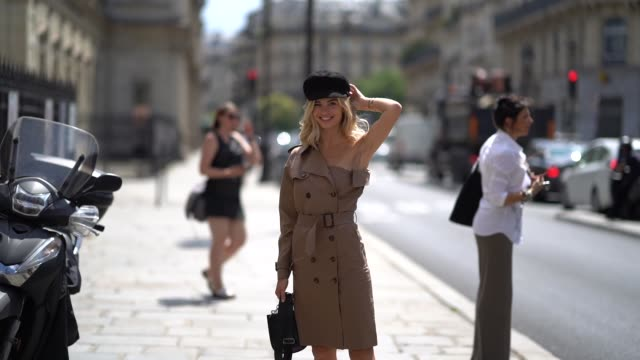 vídeos de stock, filmes e b-roll de xenia adonts wears a balck beret hat a brown offshoulder trench coat dress pink shoes outside jeanpaul gaultier during paris fashion week haute... - xenia van der woodsen