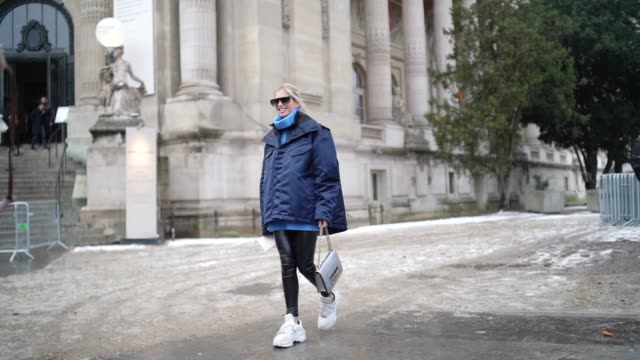 vídeos de stock, filmes e b-roll de xenia adonts wears a blue winter coat sunglasses a dior bag black leggings white sneakers shoes outside alexandre vauthier during paris fashion week... - xenia van der woodsen