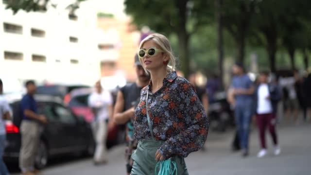 Xenia Adonts wears a floral print shirt blue high waisted flaredd pants a blue small bag sunglasses outside Acne during Paris Fashion Week Menswear...