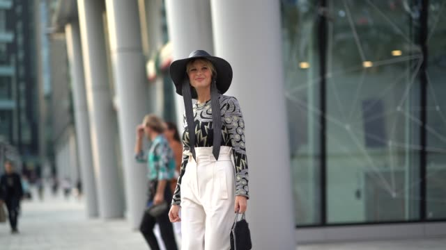 xenia adonts wears a hat a top with printed patterns white pants a bag purple shoes outside the alberta ferretti show during milan fashion week... - spring summer collection stock videos & royalty-free footage
