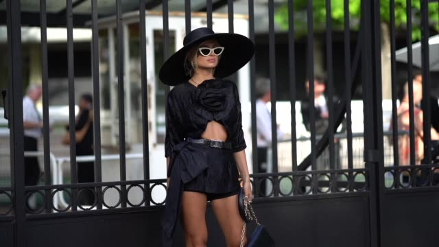 xenia adonts wears a large oversized hat, sunglasses, a black dress with attached flower, a belt, a black bag, white socks, black shoes, outside miu... - black dress stock videos & royalty-free footage