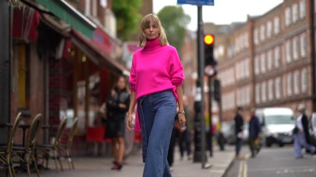 vídeos de stock, filmes e b-roll de xenia adonts wears a neon pink turtleneck wool pullover blue denim jeans pants with one flare leg gray platform boots during london fashion week... - xenia van der woodsen
