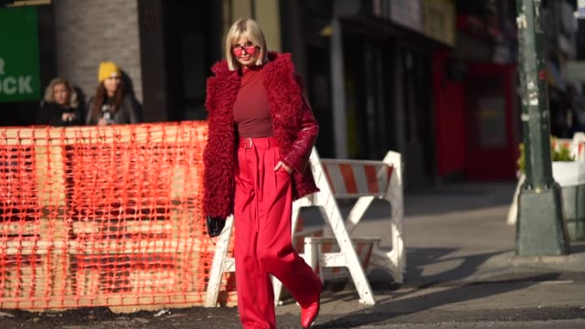 vídeos de stock, filmes e b-roll de xenia adonts wears a red turtleneck top a red leather coat with wool fluffy inner lining a belt red flare pants pointy shoes a black leather bag... - xenia van der woodsen