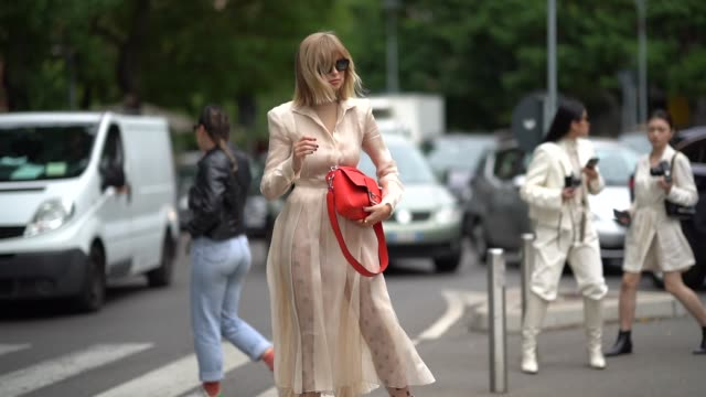 xenia adonts wears a turtleneck top a white lace mesh dress fendi tights with printed logos white boots an orange fendi bag outside the fendi show... - spring summer collection stock videos & royalty-free footage