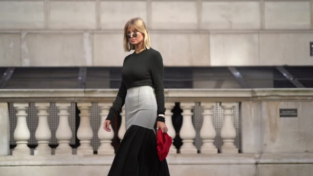 vídeos de stock, filmes e b-roll de xenia adonts wears circular sunglasses a black and gray dress with pleated part a necklace earrings a red clutch gray shiny boots during london... - xenia van der woodsen
