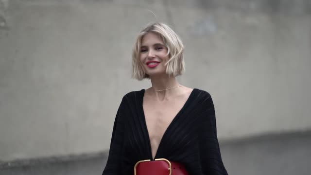xenia adonts wears earrings, a lustrous low-cut and pleated asymmetric black dress, a large red belt, black pointy kitten-heeled mules with studded... - valentino designer label stock videos & royalty-free footage
