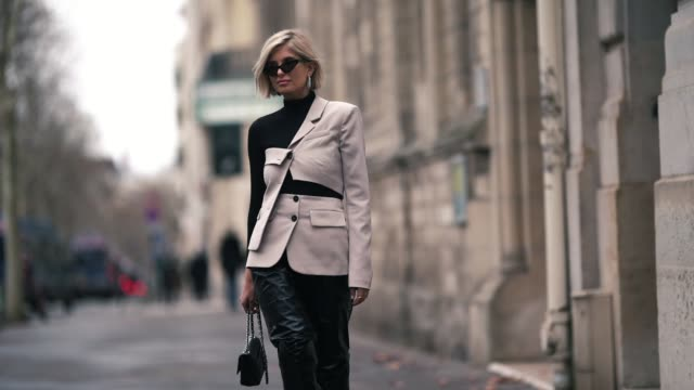 stockvideo's en b-roll-footage met xenia adonts wears earrings sunglasses a black turtleneck a beige asymmetric jacket shiny black leather pants a black chanel bag shiny black kneehigh... - coltrui