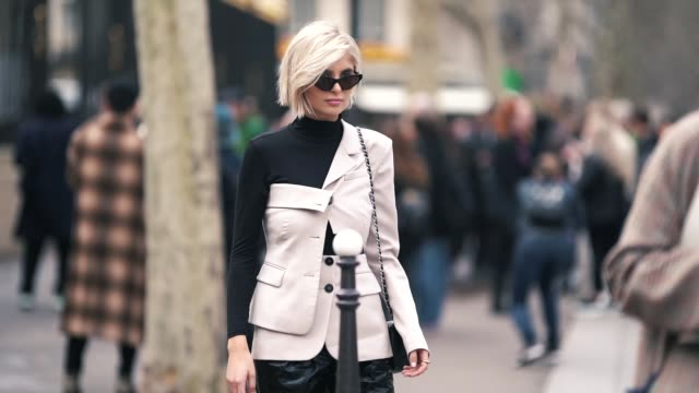 xenia adonts wears earrings sunglasses a black turtleneck a beige asymmetric jacket shiny black leather pants a black chanel bag shiny black kneehigh... - turtleneck stock videos & royalty-free footage