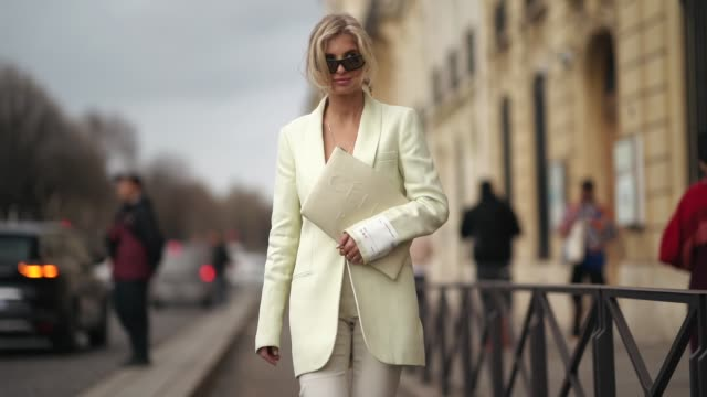 xenia adonts wears earrings, sunglasses, a cream-color jacket, white capris, a celine clutch, green and white sneakers,outside y/project, during... - street style stock videos & royalty-free footage