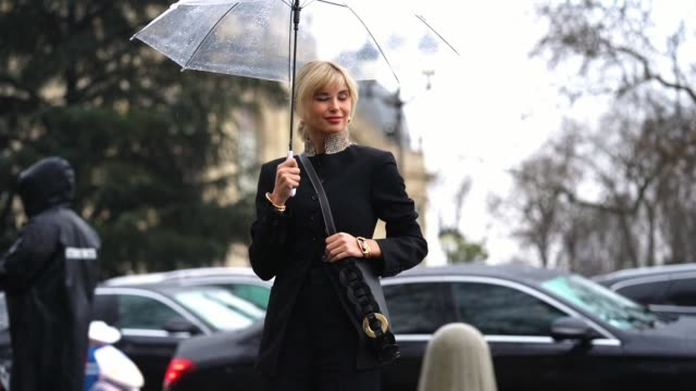 vídeos de stock, filmes e b-roll de xenia adonts wears golden earrings a black jacket with striped mandarin collar a black leather bag black cropped pants black leather shoes outside... - xenia van der woodsen