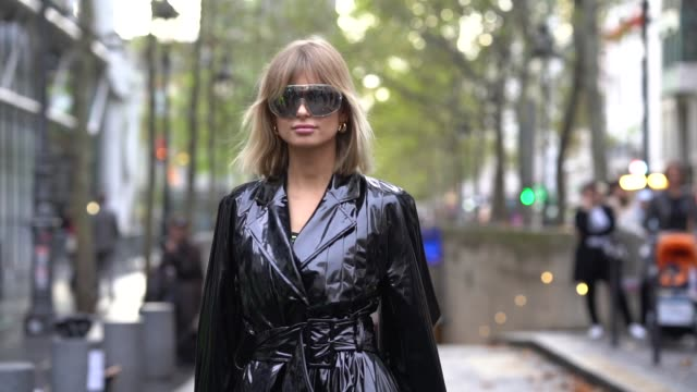 vídeos de stock, filmes e b-roll de xenia adonts wears mirrored sunglasses a shiny black vinyl trench coat black crocodile pattern pointy kneehigh boots outside koche during paris... - xenia van der woodsen