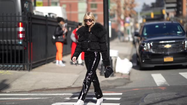vídeos de stock, filmes e b-roll de xenia adonts wears sunglasses a black fluffy coat black shiny pvc pants snake print boots a black leather bag outside longchamp during new york... - xenia van der woodsen