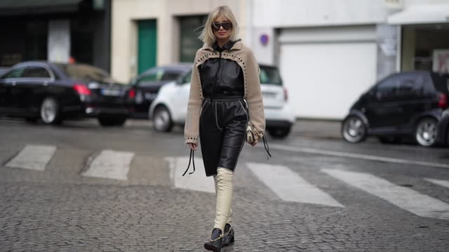 vídeos de stock, filmes e b-roll de xenia adonts wears sunglasses a black leather jumpsuit with a beige wool part and cropped leg parts black and white thigh high leather boots a chloe... - xenia van der woodsen