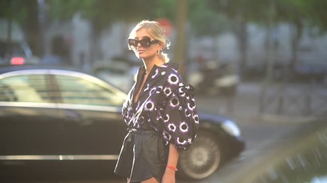 vídeos de stock, filmes e b-roll de xenia adonts wears sunglasses a floral print black and purple low neck top a golden necklace earrings outside giambattista valli during paris fashion... - xenia van der woodsen