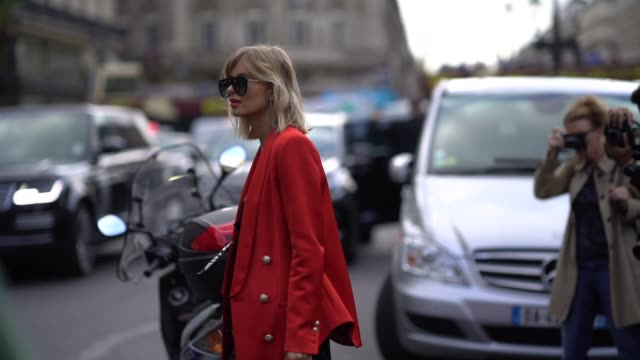 vídeos de stock, filmes e b-roll de xenia adonts wears sunglasses a red oversized blazer jacket a balmain logo bag a black dress black leather boots with metallic heels outside balmain... - xenia van der woodsen