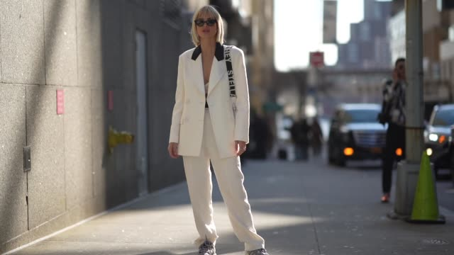 vídeos de stock, filmes e b-roll de xenia adonts wears sunglasses a white oversized jacket with black collar white pants sneakers a bag outside tory burch during new york fashion week... - xenia van der woodsen