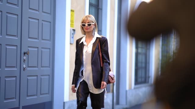 stockvideo's en b-roll-footage met xenia adonts wears white sunglasses a black leather jacket a white shirt leather shorts black shiny long pointy boots outside tod's during milan... - zwart jak