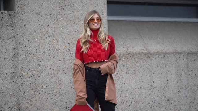 Xenia Van Der Woodsen 'Overdose' wears sunglasses a red turtleneck bare belly pullover jeans white boots a brown coat during London Fashion Week...