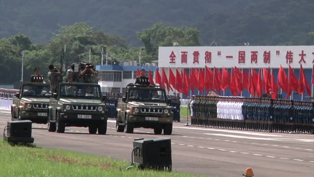 xi jinping china's president center right rides in a vehicle as he reviews people's liberation army troops at the shek kong barracks in hong kong... - 行進する点の映像素材/bロール