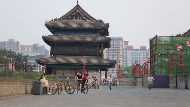 Young people ride bicycle on the ancient Xian old city wallThis wall was built several years ago