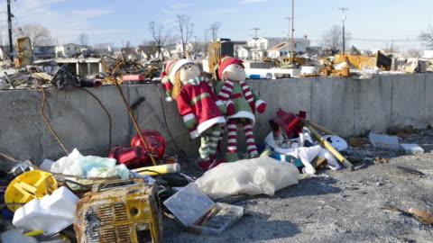 vidéos et rushes de xmas dolls leaning against whats left of a house with destruction in background - ruiné