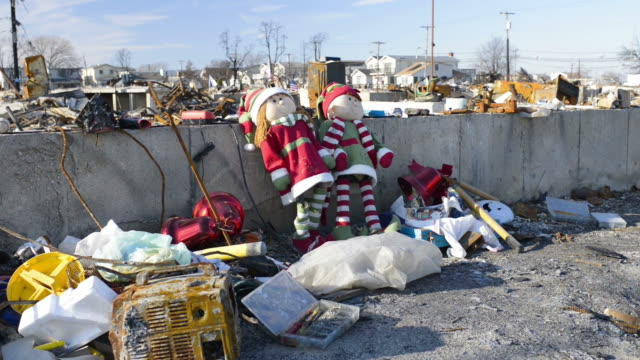 Xmas dolls leaning against whats left of a house with destruction in background