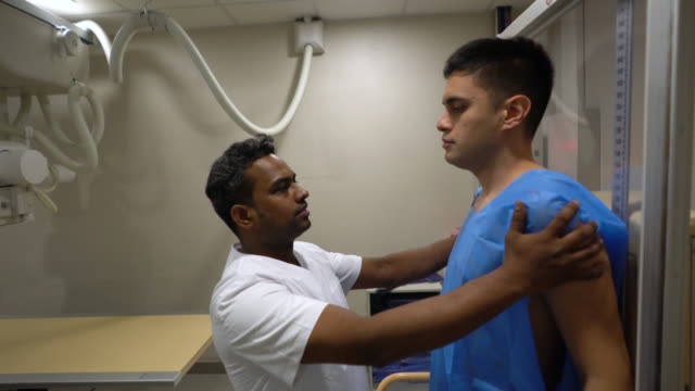 x-ray technician getting a patient ready for a chest x-ray - x ray equipment stock videos & royalty-free footage