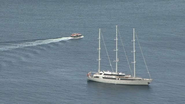 vídeos de stock, filmes e b-roll de ws yacht at anchor and boat cruising through sea / dubrovni, croatia  - passear sem destino