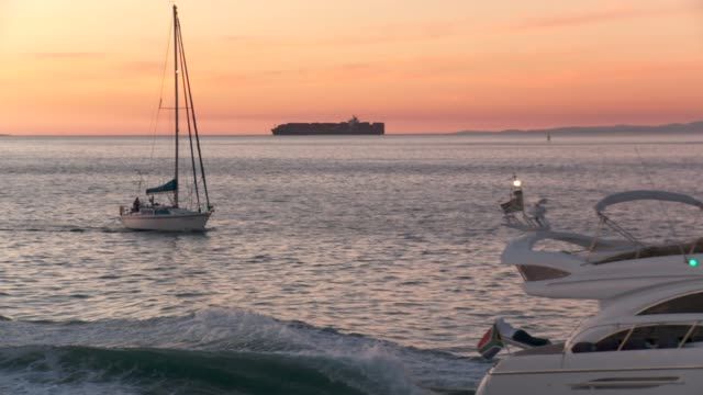vídeos y material grabado en eventos de stock de a yacht cruises past a sailboat at sunset available in hd. - pasear en coche sin destino