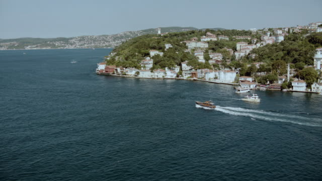 aerial a yacht down the bosphorus strait past waterfront homes / istanbul, turkey - july 15 martyrs' bridge stock videos & royalty-free footage