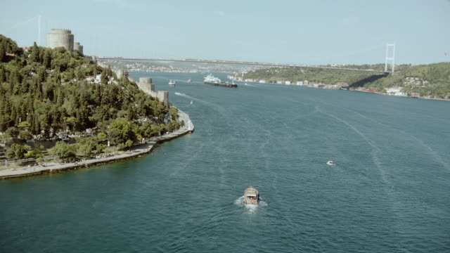 aerial a yacht drives out to sea on the bosphorus strait / istanbul, turkey - july 15 martyrs' bridge stock videos & royalty-free footage